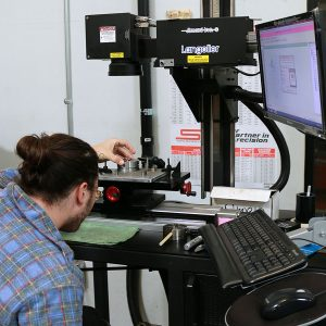 Laser marking is done in this department. Taylor loads a chuck to receive its laser engraved markings.