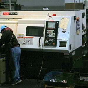 A CNC lathe operator monitors progress of a job.